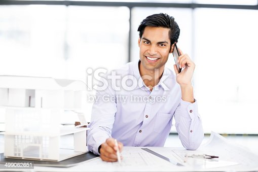 Portrait of smiling male architect examining blueprint while answering smart phone at desk in office. Horizontal shot.