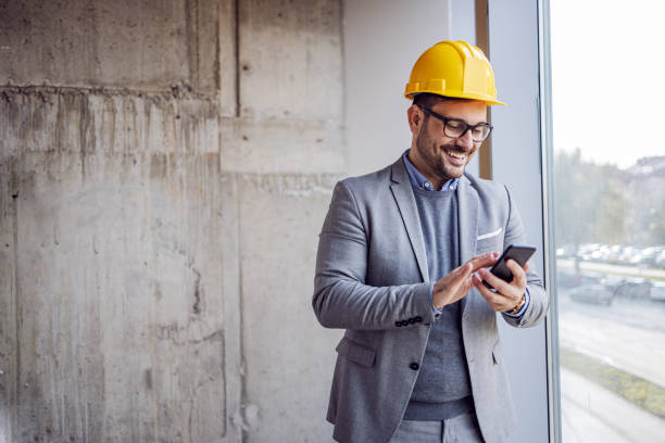 Smiling architect in suit and with helmet on head standing in building in construction process next to window and typing message on smart phone. stock photo