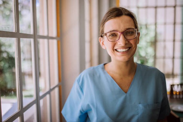 Smiling Argentinian female nurse in medical scrubs stock photo