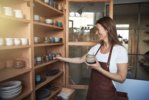 Smiling artisan organizing pottery on shelves in her creative gallary