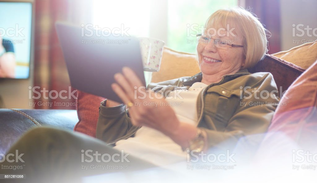 smiling as she has a cup of tea and a read stock photo