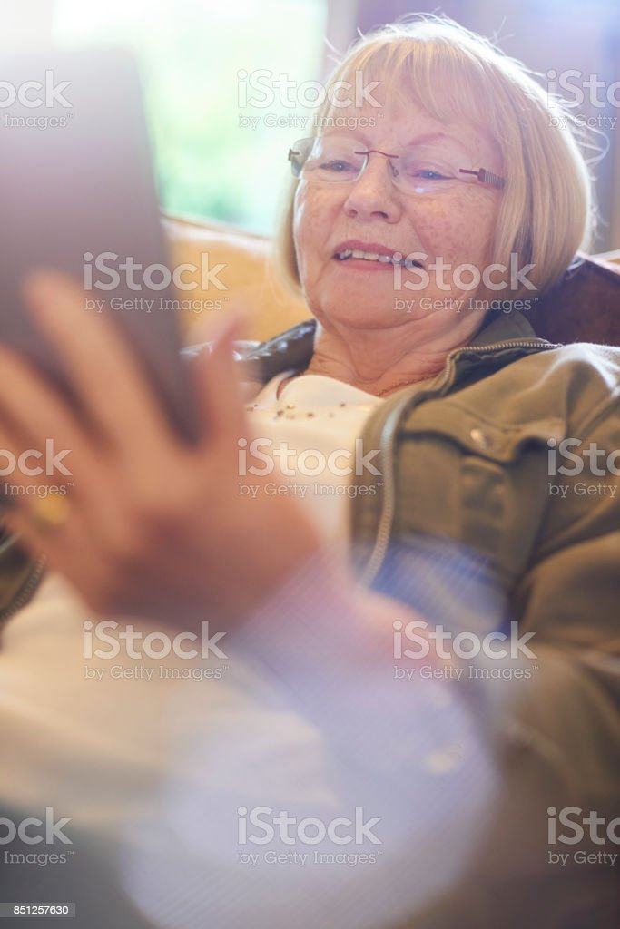 smiling as she reads on digital tablet stock photo