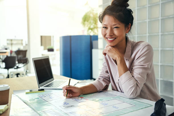 Smiling Asian architect working on blueprints at an office desk stock photo