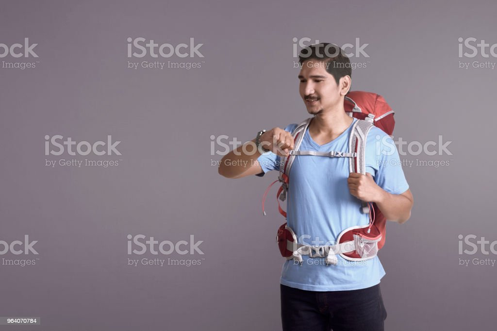 Smiling asian backpacker checking the watch - Royalty-free Adult Stock Photo