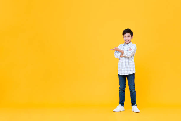 Smiling Asian boy doing arms crossed gesture with open palm stock photo