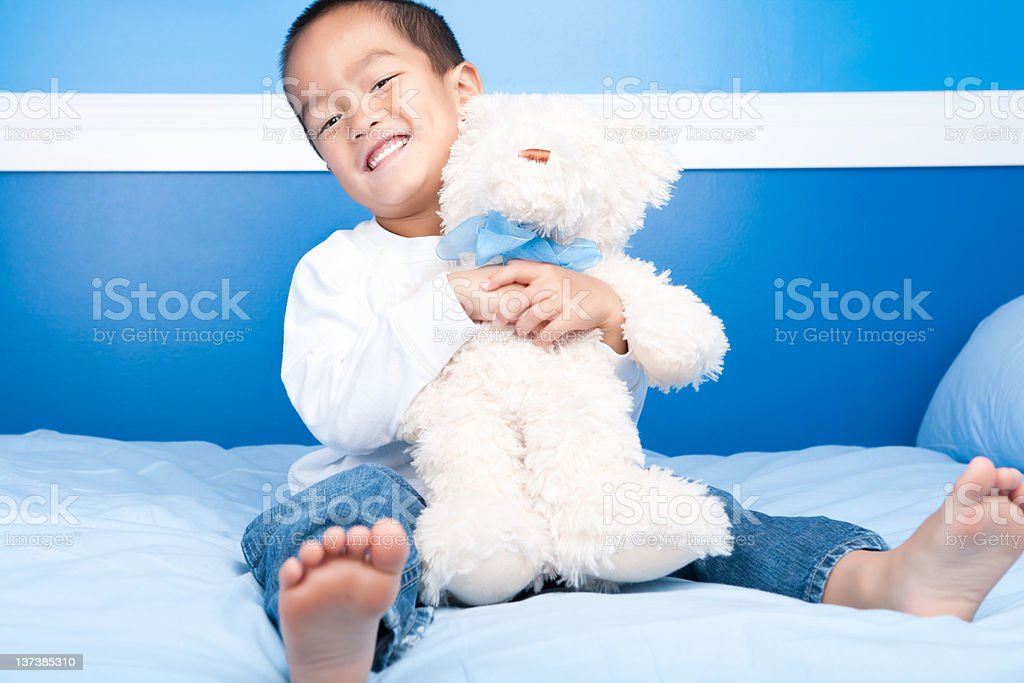 Smiling asian boy hugging teddy bear in bed stock photo