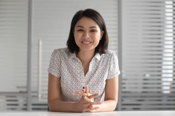 Lächelnde asiatische Geschäftsfrau, die auf Kamera-Shooting-Video-Training schaut – Foto