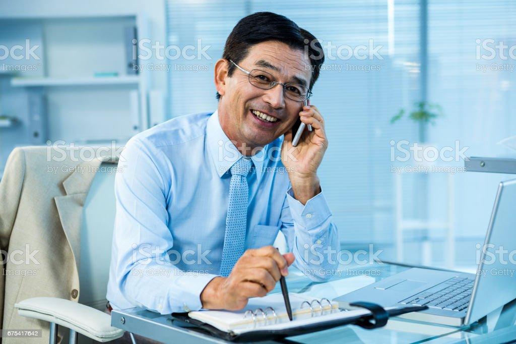Homme d'affaires asiatique, appeler quelqu'un de souriant photo libre de droits