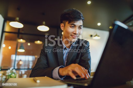 istock Smiling asian businessman in suit working with laptop 845530100