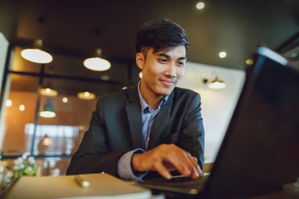 微笑亞洲商人穿著使用筆記本電腦 - 亞洲 個照片及圖片檔