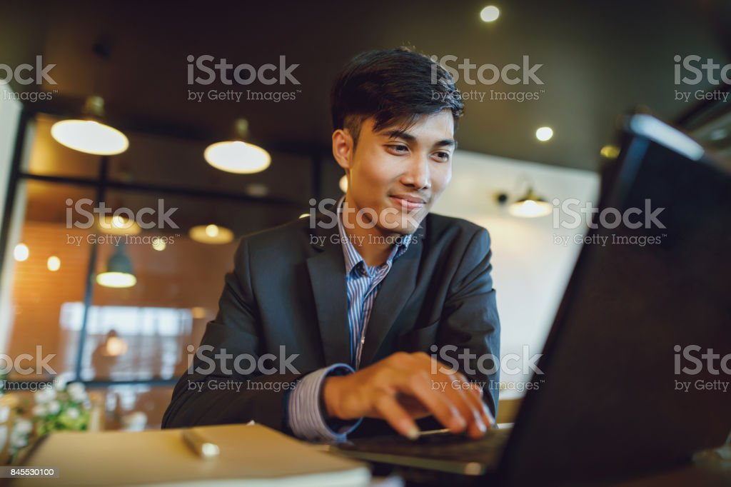 Smiling asian businessman in suit working with laptop stock photo