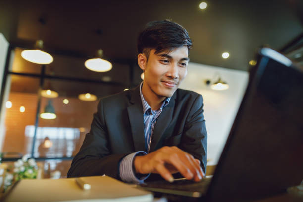smiling asian businessman in suit working with laptop - asia stock pictures, royalty-free photos & images