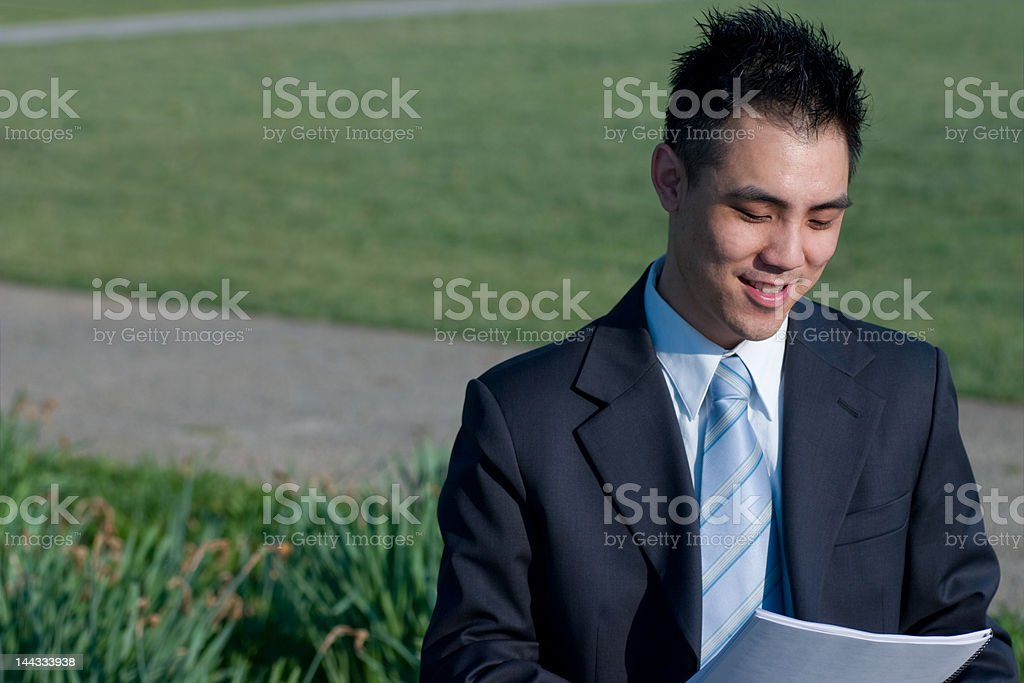 Smiling Asian Businessman Reading Outside royalty-free stock photo