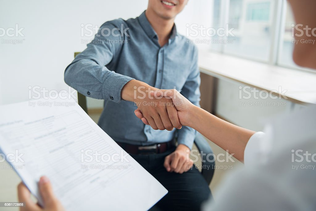 Smiling Asian businessman shaking partners hand - Royalty-free Adult Stock Photo