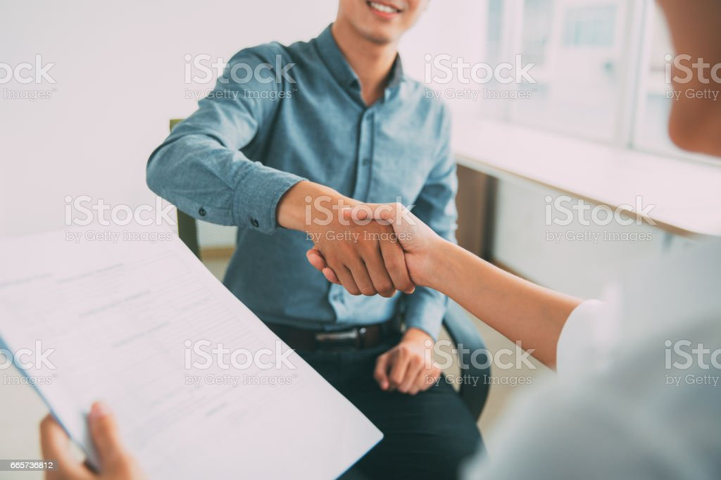 Smiling Asian businessman shaking partners hand Smiling Asian businessman wearing shirt sitting in office and shaking hand of female partner. Woman holding document Adult Stock Photo