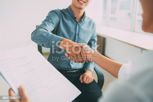 istock Smiling Asian businessman shaking partners hand 665736812