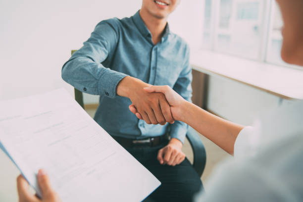 Smiling Asian businessman shaking partners hand - foto stock