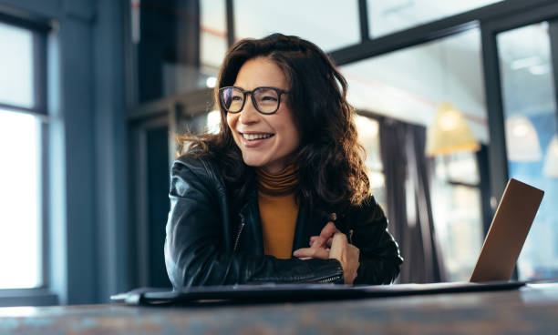 Smiling asian businesswoman at office Woman sitting at the desk with laptop looking away and smiling. Asian woman in casuals at office. looking away stock pictures, royalty-free photos & images