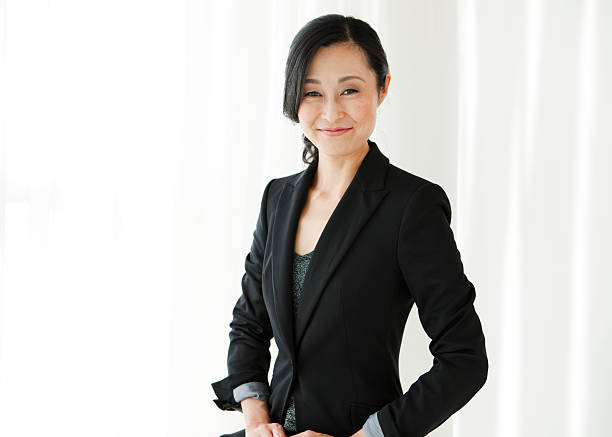 Smiling Asian businesswoman in black suit stock photo