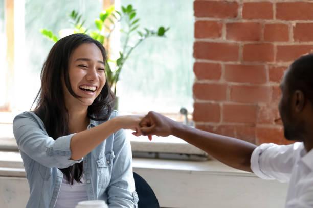 sonriente mujer de negocios asiática con los puños de colega afroamericano - high five fotografías e imágenes de stock