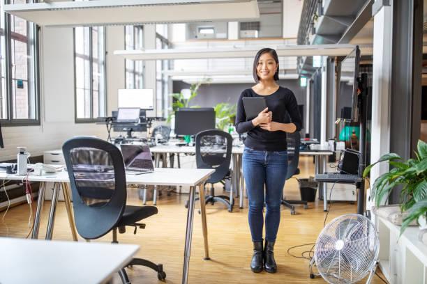 デジタルテーブルを持つアジアの実業家と微笑む - 東洋民族 ストックフォトと画像