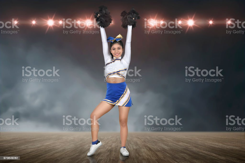 Smiling asian cheerleader perform with pom-poms stock photo