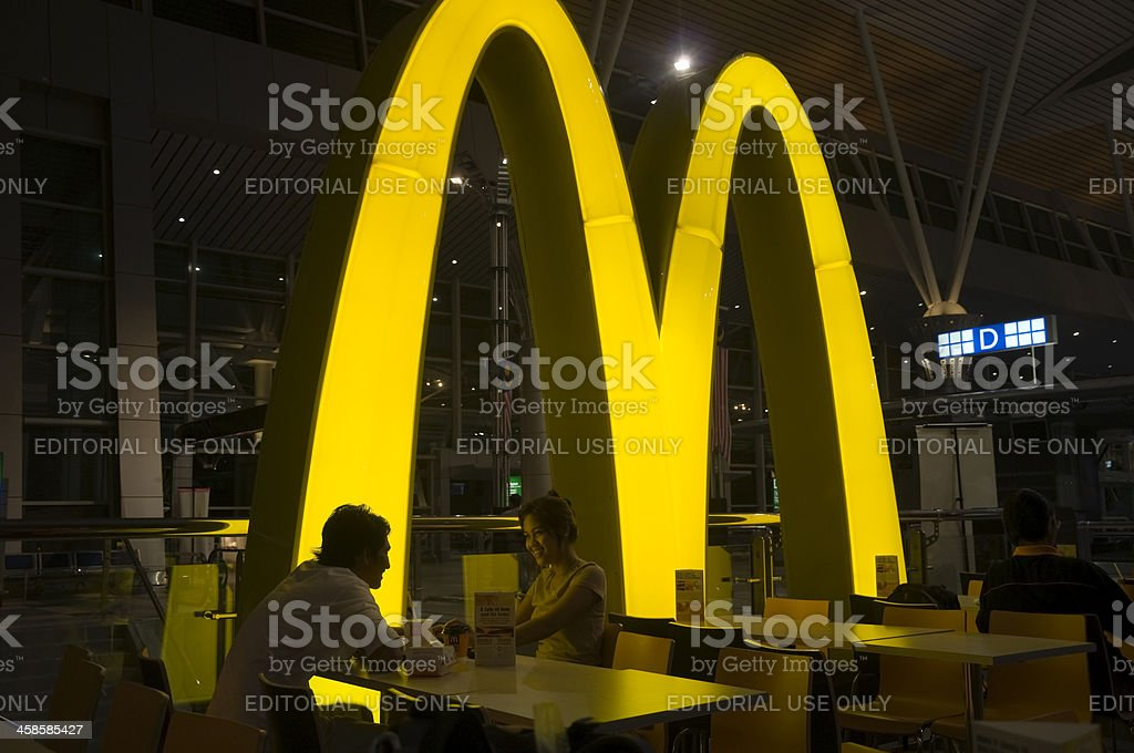 Smiling asian couple eating in McDonalds restaurant stock photo