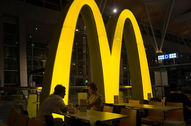 улыбающаяся азиатская пара еды в ресторан mcdonalds - mcdonalds стоковые фото и изображения