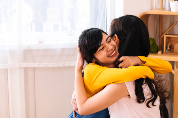 Smiling Asian daughter hugging her mother in living room at home stock photo