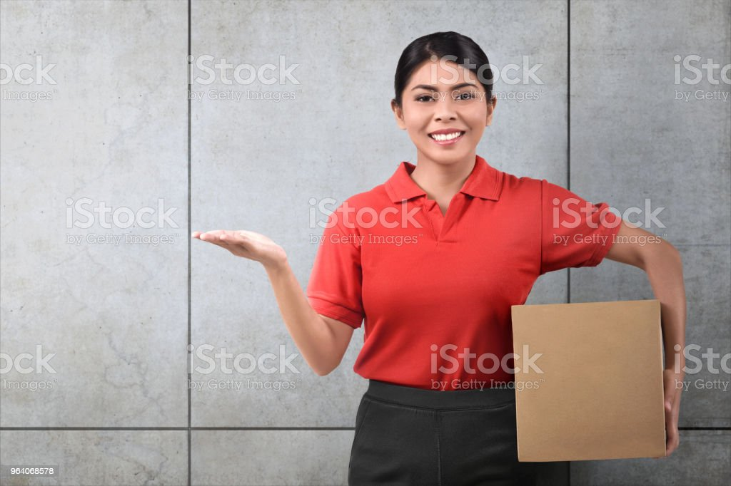 Smiling asian delivery woman with parcel - Royalty-free Adult Stock Photo