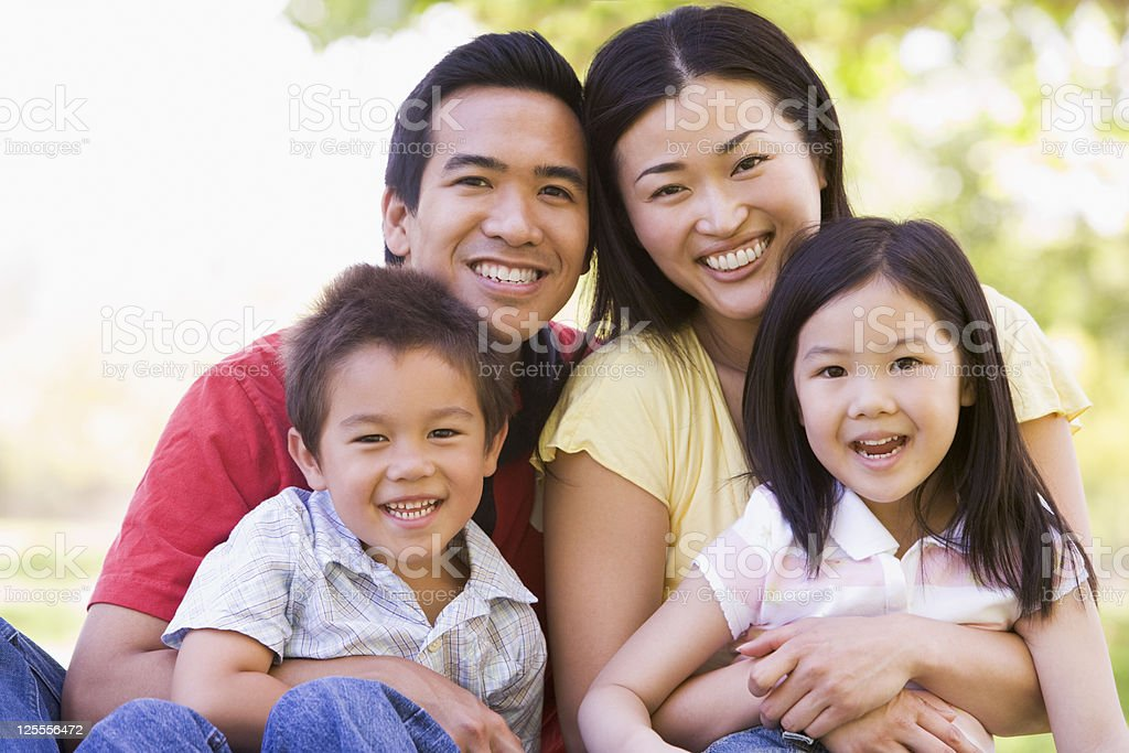 Smiling Asian family of four outdoors stock photo