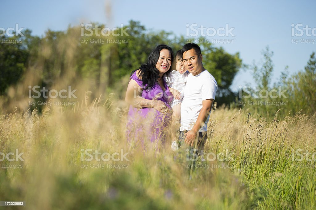 Smiling asian family portrait in grass field royalty-free stock photo