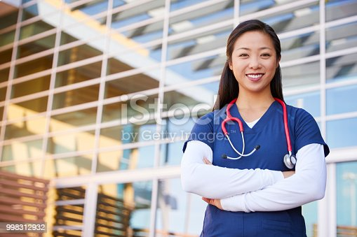 istock Smiling Asian female healthcare worker with arms crossed 998312932