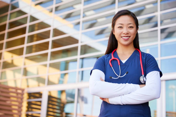 Smiling Asian female healthcare worker with arms crossed stock photo