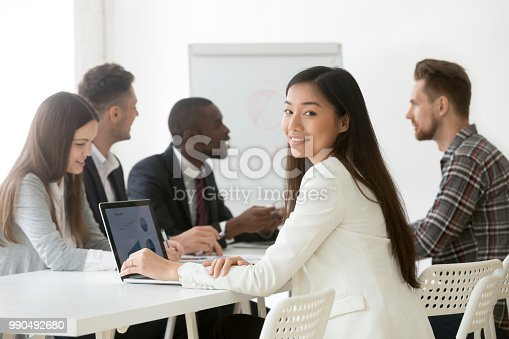istock Smiling Asian female posing to camera working during briefing 990492680