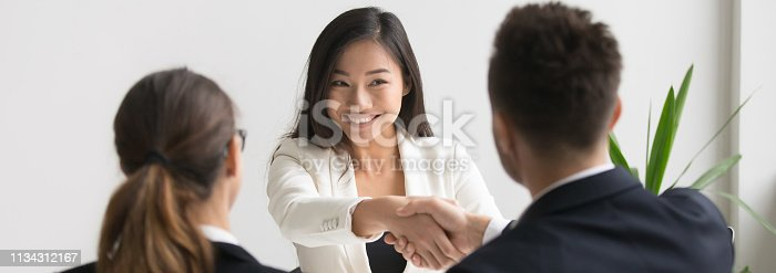 istock Smiling asian female vacancy candidate shaking hand with hr manager 1134312167