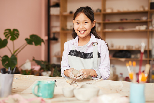 Smiling Asian Girl Enjoying Pottery Class