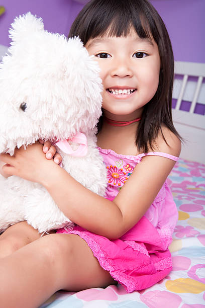 lächelnd asiatische mädchen umarmen teddybär im bett - lila mädchen zimmer stock-fotos und bilder