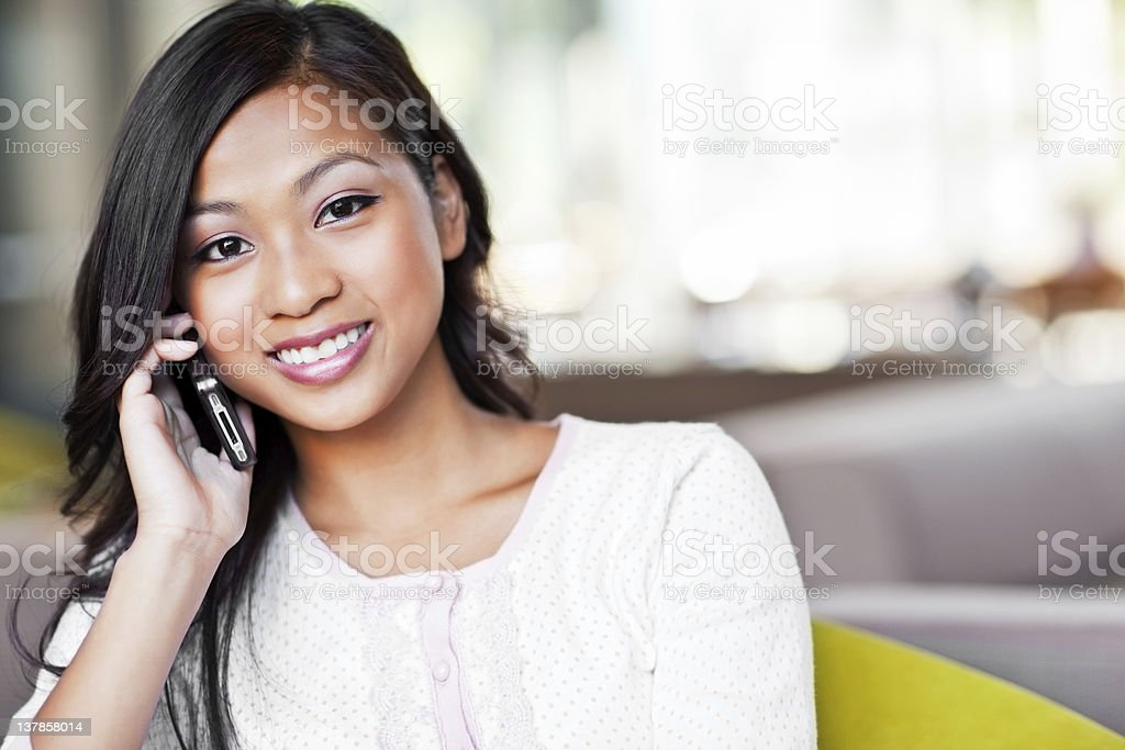 Smiling Asian girl in a white sweater on a cell phone royalty-free stock photo