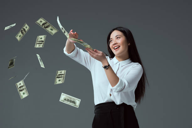 smiling asian girl throwing dollar banknotes isolated on grey - throw money away stock pictures, royalty-free photos & images