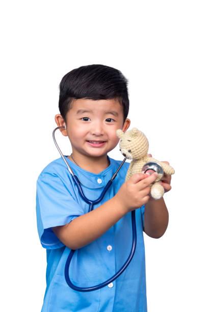 Asyalı çocuk beyaz kırpma yoluyla izole stetoskop tutan mavi tıbbi üniformalı gülümseyerek. stok fotoğrafı