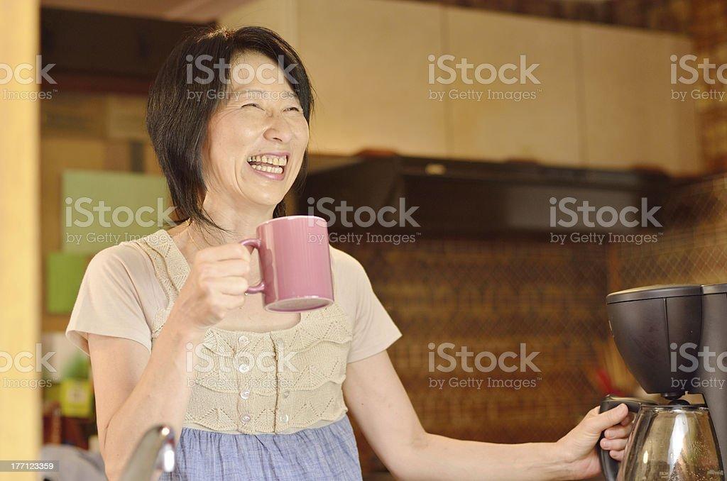 笑顔アジアの女性が家庭でのコーヒー - 40代のロイヤリティフリーストックフォト