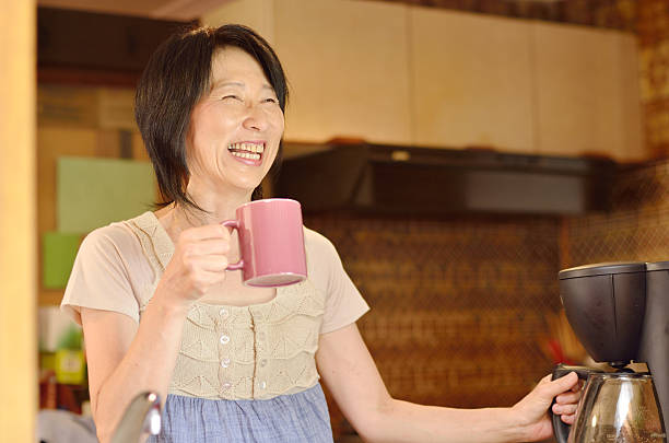 smiling asian lady having coffee at home - stay at home parent stock pictures, royalty-free photos & images