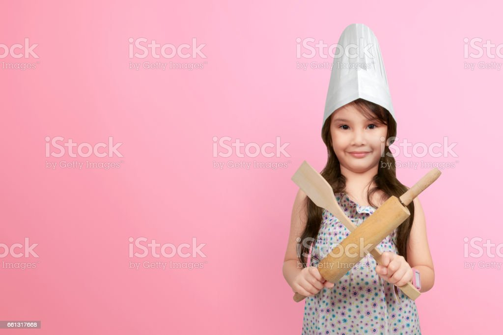 Smiling asian little girl in chef hat holding wooden cooking utensils stock photo