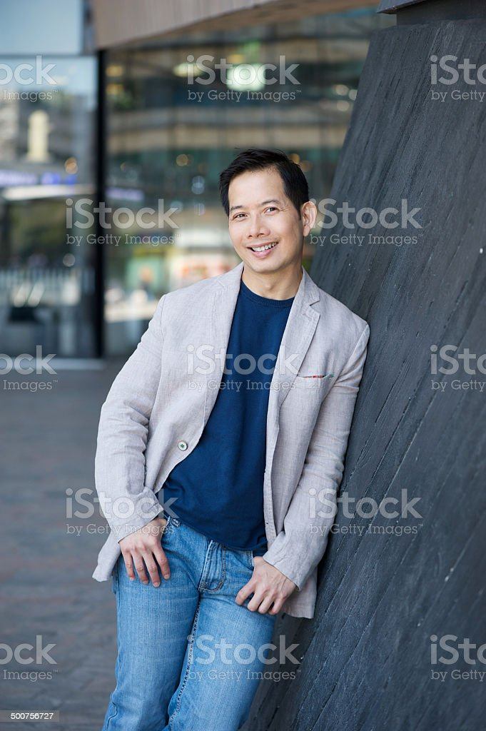 Smiling asian man posing outdoors stock photo