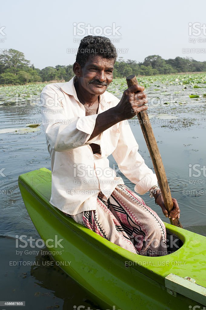 Smiling Asian man row a small traditional boat royalty-free stock photo