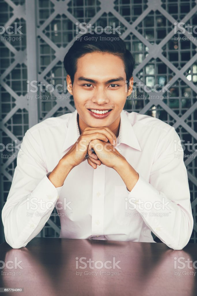 Smiling Asian Man Sitting with Hands Under Chin stock photo