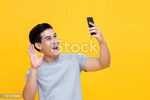 Young smiling  handsome Asian man saying hi and waving hand while making video call on smarphone isolated on yellow background