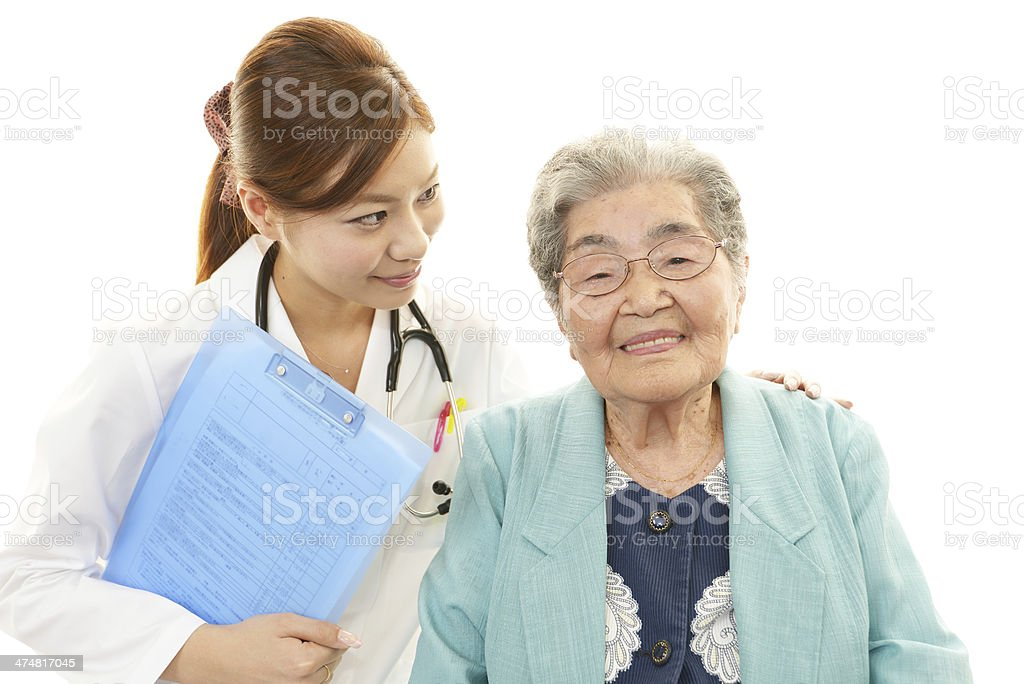Smiling Asian medical doctor and senior woman royalty-free stock photo