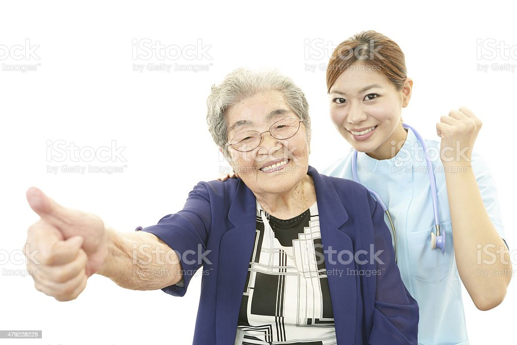 Smiling Asian nurse with old woman stock photo